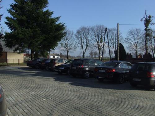 Utwardzony plac naprzeciwko kościoła, wykorzystywany jako parking lub miejsce organizacji odpustów (inwestycja gminy).